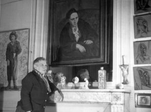 PARIS, FRANCE: US writer Gertrude Stein (1874-1946) poses in front of the portrait of her that Picasso painted in 1906, at her Parisian apartment in an undated photograph. Stein studied psychology and medicine in the United States, then settled in Paris where she was absorbed into the world of experimental art and letters. She was revered as a critic in Paris, and her home became a salon for artists and writers between the two World Wars. (Photo credit should read AFP/AFP/Getty Images)